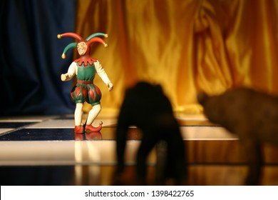 LAGUNA BEACH, CALIFORNIA/USA - NOVEMBER 25, 2006: Court jester Schleich figurine standing in court with spotlight on him with chimpanzee and hyena figurines in foreground in shadow. - Image