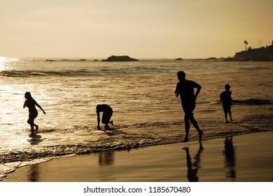 Laguna Beach, USA March 25, 2008 A family enjoys wading in the ocean at Laguna Beach, California near sunset