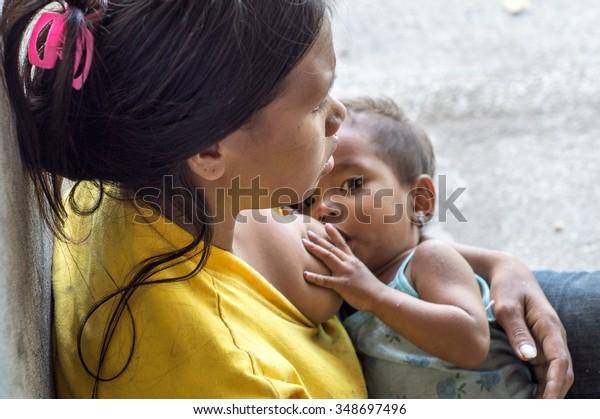 LAGUNA, PHILIPPINES - DECEMBER 4, 2015: Woman breast feeding a child seeking alms at church portal ruins.  A common scene found in many Third World Countries.