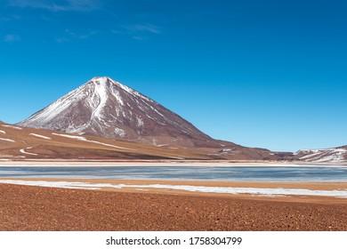 The Laguna Verde or Green Lagoon in winter with the Licancabur volcano in the snow, Eduardo Avaroa Andean Fauna National Reserve, Uyuni salt flat region, Bolivia.