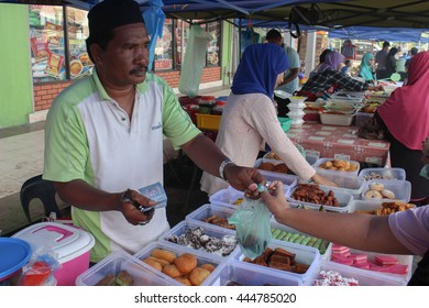 Lahad Datu Sabah Malaysia- June 25, 2016:  Buying delicious Malaysian home cooked local 'kueh' (cakes) at food bazaar during the month of Ramadan