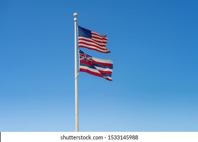 Lahaina, HI / USA – September 27, 2019: Flag pole in Lahaina, Hawaii with the flags of the United States and the state of Hawaii.