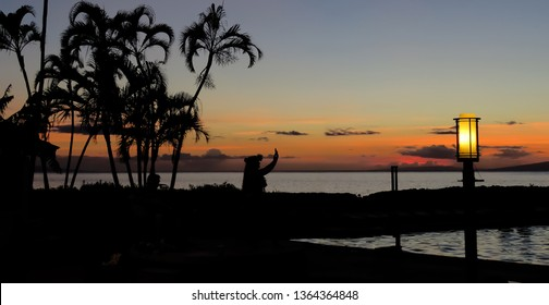 Lahaina, Maui, Hawaii - 07/22/2015: Silhouette of a Hawaiian hula dancer performing near the ocean at sunset with palm trees on the beach, Lahaina, Maui, Hawaii