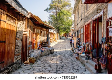 LAHIC, AZERBAIJAN - Sep 02, 2017. Street view on cobblestone Huseynov street, the main street of Lahic mountainous village of Azerbaijan, with buildings, shops and people.