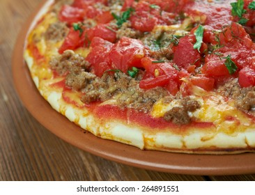 Lahmacun - round, thin piece of dough topped with minced meat and minced vegetables