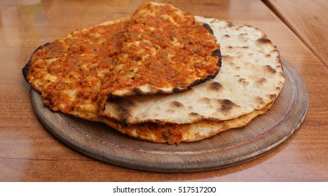 Lahmacun, traditional Turkish food. A round, thin piece of dough topped with minced meat, vegetables and spices, then baked. Lemon, parsley and Urfa pepper isot.
