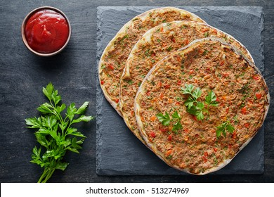 Lahmacun traditional turkish pizza with minced beef or lamb meat, paprika tomatoes, parsley baked spicy food on dark table background