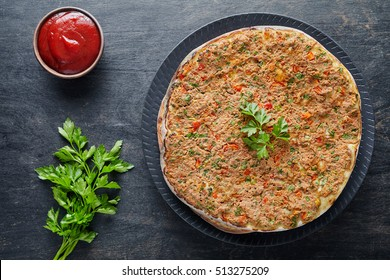 Lahmacun traditional turkish restaurant pizza with minced beef or lamb meat, paprika, tomatoes, cumin spice, parsley baked spicy middle eastern food on dark table background