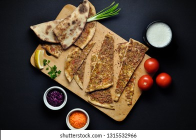 Lahmacun, Turkish pizza on a dark table with veggies and ayran