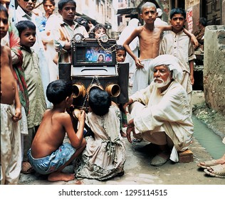 Lahore: dated 12/05/2001, An old man operating Bioscope inside walled city street, children watched and enjoy very much, nowadays this street cinema disappeared, district of Lahore, Punjab, Pakistan.