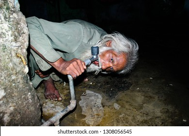 Lahore: Not water in pipeline but An old man trying to drinking water by water pipe, many places problem of shortage water, province of Punjab, Pakistan dated 22/12/2014.