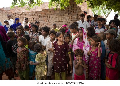 LAHORE, PAKISTAN- AUG 2: Unidentified children and women as a slavery in brick kiln, are waiting for the food from relief team on August 2 2012 in Lahore, Pakistan.