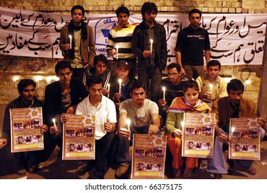 """LAHORE, PAKISTAN - DEC 01: Lahore University of Management Sciences (LUMS) students hold lightened candles during """"Peace Message Rally"""" at press club on December 01, 2010 in Lahore, Pakistan."""