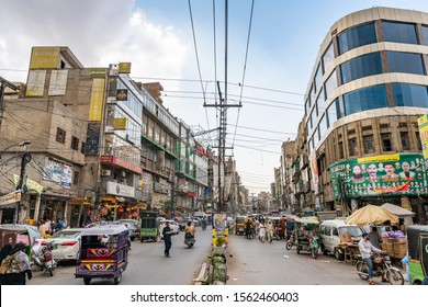LAHORE, PAKISTAN - JUNE 2019: Shah Alami Road Entrance into the Walled City with Busy Traffic and Stores on a Cloudy Day