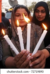 LAHORE, PAKISTAN - MAR 07: Supporter of Kashaf Foundation holds lightened candles during demonstration on occasion of the 'World Women Day' on Monday, March 07, 2011in Lahore.