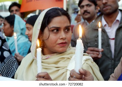 LAHORE, PAKISTAN - MAR 07:  Supporters of Kashaf Foundation hold lightened candles during demonstration on occasion of the 'World Women Day' on  March 07, 2011 in Lahore.