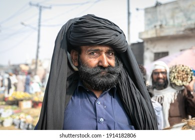 Lahore, Pakistan - October 2019: Bearded Man in traditional turban