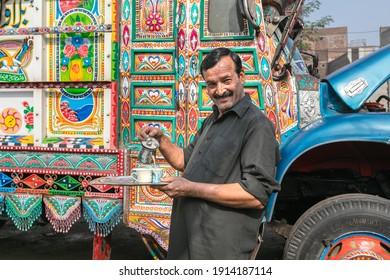 Lahore, Pakistan - October 2019: Man drinking tea near Pakistani colorful truck