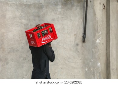 Lahore,Pakistan,July-26 2018:Worker carry emply cool drink bottles