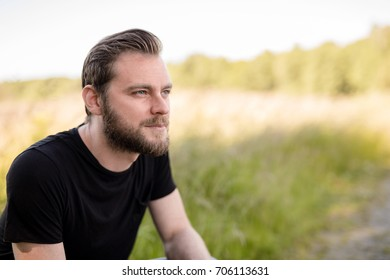 Laid back bearded man wearing a black shirt, standing outdoors on a sunny summer day looking away from camera with a smile on his face.