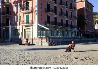 Laigueglia (SV), Italy - February 15, 2017: Tourist relaxing at Laigueglia beach, Riviera dei Fiori, Savona, Liguria, Italy.