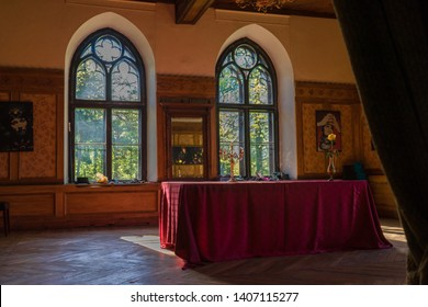 Laitse / Estonia - May 12 2018: Colorful dining room in romantic Laitse manor. Table covered with crimson red cloth, high arched windows with stained glass. Sunlight warming the empty room.