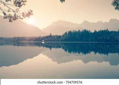 Lake in Alps with mountains on background, toned photo. Landscape in summer morning