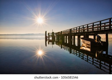 Lake Ammersee in Bavaria on an early morning bevor an shortly after sunrise. The lake with a little pier and the reflexion of an sunstar