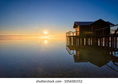 Lake Ammersee in Bavaria on an early morning bevor an shortly after sunrise. The lake with a little boathouse in the foreground