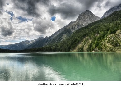 Lake of Anterselva surrounded by mountains with blue sky and dark clouds in the background on a summer day, Sud Tirol, Italy