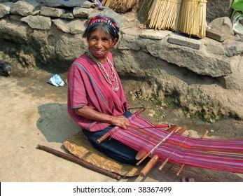 LAKE ATITLAN, GUATEMALA-MAY 15: Mayan woman performs traditional craft of weaving on a primitive loom May 15, 2009 in Lake Atitlan, Guatemala.