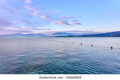 Lake Attersee at Seewalchen, Salzkammergut in the morning with orange red buoys on the water