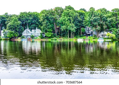 Lake Audubon with lakefront waterfront houses in Reston, Virginia with reflection of summer green foliage on trees