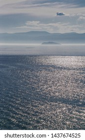 Lake Baikal in the afternoon light. Glare of sunlight on the surface of lake Baikal. Beautiful picture of lake Baikal. Russia. Siberia. Baikal. Olkhon Island.