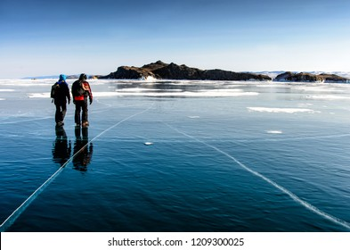 Lake Baikal is covered with ice and snow, strong cold, thick clear blue ice. Icicles hang from the rocks. Lake Baikal is a frosty winter day. Amazing place, Beauty of Russia with walking men on ice