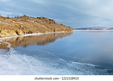Lake Baikal in December. Coastal rocks are reflected in thin blue transparent ice on a sunny frosty day