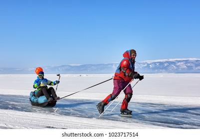 LAKE BAIKAL, IRKUTSK REGION, RUSSIA - March 08, 2017: Satisfied man is rolling woman sitting in sledge drag. Cheerful active rest in winter in Siberia