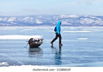 LAKE BAIKAL, IRKUTSK REGION, RUSSIA -  March 07, 2016: Tourist is hiking on the winter Lake Baikal, Irkutsk region, Russia
