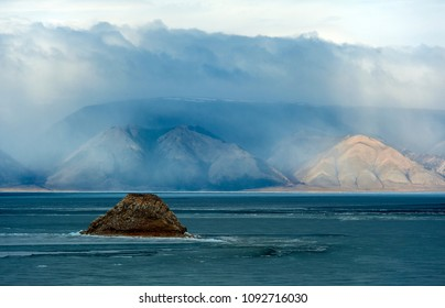 Lake Baikal and mountains with clouds above them, view from Olkhon