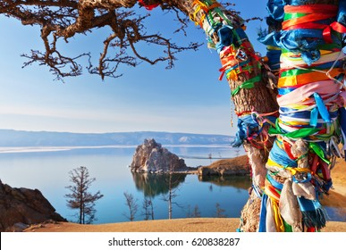 Lake Baikal. Olkhon Island. Colored ribbons tied on a Wish Tree against the background of a spring ice drift and the Shamanka Rock