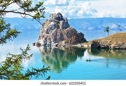 Lake Baikal. Olkhon Island. Tourists sail on a rubber boat near the Shamanka Rock. Summer vacation on the lake