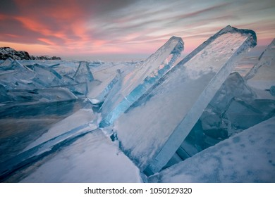 Lake Baikal at sunset, everything is covered with ice and snow, thick clear blue ice. Lake Baikal in the rays of the setting sun. Amazing place, UNESCO world heritage