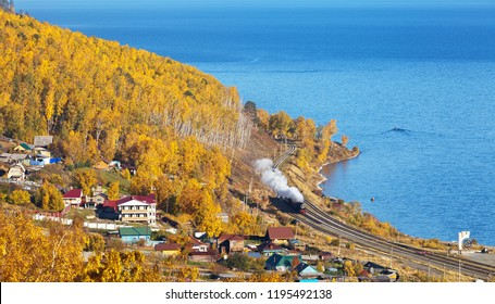 Lake Baikal. View of the Circum-Baikal Railway from above on an autumn day. Tourist excursion historic locomotive arrives in the village of Kultuk. Tourists take pictures of the train