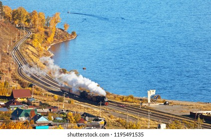Lake Baikal. Village Kultuk. A tourist sightseeing train moves along the Circum-Baikal Railway on autumn day (On road stela there is inscription Circum-Baikal railway and the shape of Lake Baikal)