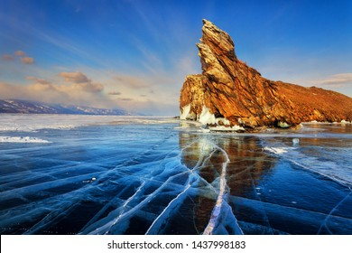 Lake Baikal in winter. Beautiful rocky island on a background of blue sky and smooth ice with cracks