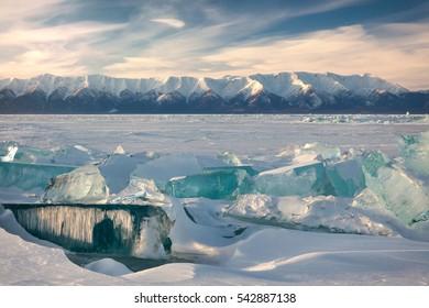 Lake Baikal in winter. Ice hummlocks and icicles on foreground. Mountains of Svyatoy Nos peninsula on background