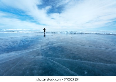 Lake Baikal in the winter. Silhouette of a lonely photographer against the background of an endless ice desert