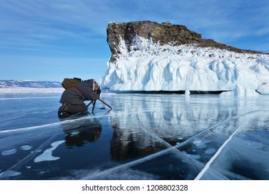 Lake Baikal in winter. A tourist on blue ice photographs a beautiful icy rock on a cape Kobyliya Golova or Horin-Irgi. Winter photo tours on Olkhon Island