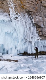 Lake Baikal in the winter. An unknown tourist with a mobile phone takes pictures unusual long icicles on the icy coastal cliffs of Olkhon Island. Ice travel