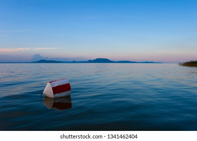 Lake Balaton with the Badacsony mountan in the background after sunset with a buoy in the foreground